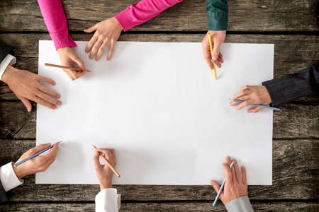 team ideas: Teamwork and cooperation concept - top view of six people - men and women - drawing or writing on a large white blank sheet of paper.