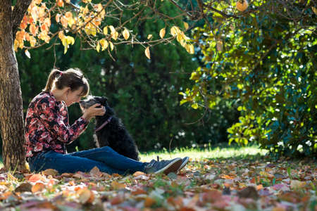 endear: Young woman sitting under a colorful autumn tree lovingly petting her black dog as they join their noses in affection.