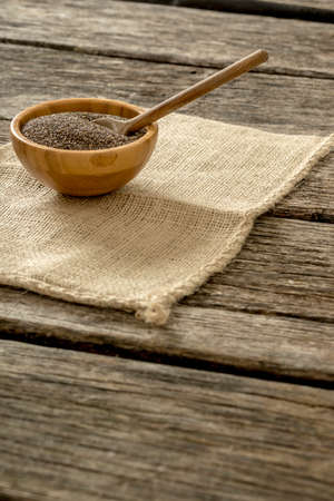burlap sac: Chia seeds in a wooden bowl with wooden spoon in it on a burlap sac lying over textured rustic desk.