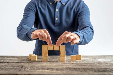 木製キューブで橋を作る男のフロント ビュー。ビジネス、教育、建設の概念。