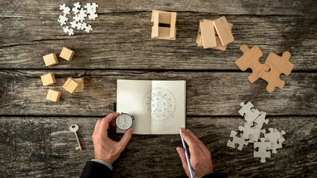 new business problems: Businessman making plan and business strategy decisions as he sketches a compass he is holding into his notebook. Various cubes, pegs, puzzles and a key lying on his wooden office desk, top view.