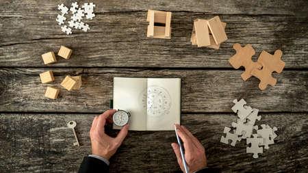 Podnikatel plán a obchodní strategie rozhodování, jak se načrtává kompas on je drží do notesu. Různé kostky, kolíky, hádanky a klíč ležel na dřevěném kanceláři, pohled shora. Reklamní fotografie