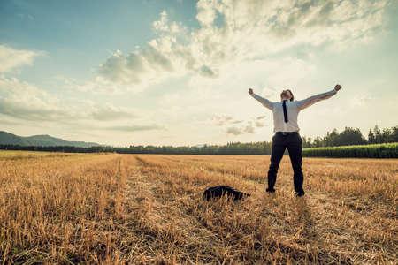 Imprenditore di successo in piedi vittoriosamente nel mezzo del campo di sollevare le braccia in festa e sollievo mentre si trova sotto il cielo di sera maestoso con la sua giacca, sdraiato sul pavimento accanto a lui. Archivio Fotografico