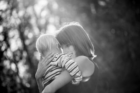 Black and white image of a happy smiling young mother hugging her baby boy outside in a ray of bright sun.