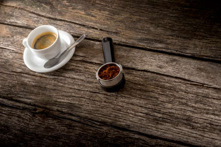 black boards: Cup of fresh hot Arabica black coffee and freshly ground coffee beans in the metal measure of a coffee machine lying on a textured rustic wooden boards. Focus to the ground coffee powder. Stock Photo