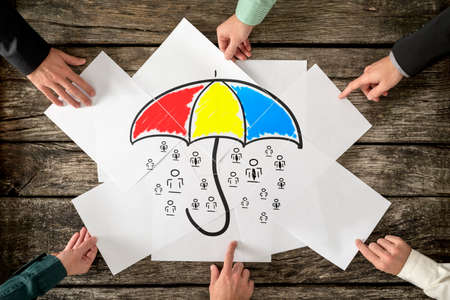 Safety and life insurance concept - six hands assembling a colourful umbrella sheltering many people icons drawn on white papers. Stockfoto