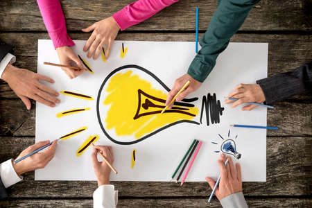 group of hands: Top view of six people, men and women, drawing bright yellow light bulb on a large sheet of paper or placard. Conceptual of teamwork, research, education and innovation.