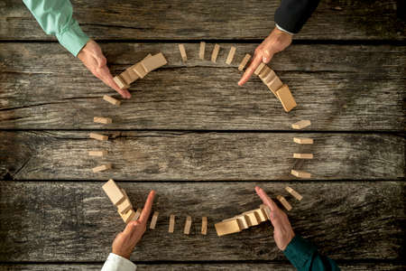 Hands of four businessmen joining forces  as a team to stop wooden pegs from falling. Business concept of teamwork, crisis solution and problem management.