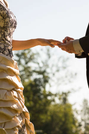 wedding bride: Closeup of groom placing a wedding ring on his brides finger outside on a sunny day. Stock Photo