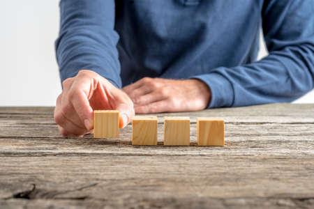 cubo: Vista frontal de la mano masculina la colocación de cuatro cubos de madera en blanco en una fila en un escritorio de madera rústica con textura.