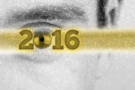 superimposed: Creative 2016 New Year background with the date in a golden banner superimposed over a greyscale face of a man with the eye forming the 0 in the date and falling snow flakes with copyspace.