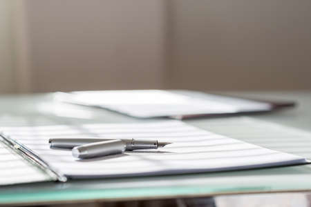 Nízký úhel pohledu na stříbrné inkoustové pero ležící na bílém listu papíru ve složce s jinou sadou papírování na opačné straně stolu.