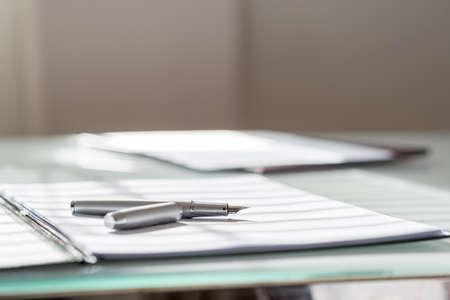 legal document: Ángulo de visión baja de la pluma de tinta de plata miente en la hoja de papel blanco en una carpeta con otra serie de trámites en el lado opuesto de la mesa. Foto de archivo