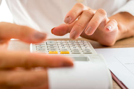 banker: Front view of female banker calculating expenses and income using adding machine while checking a printout receipt.