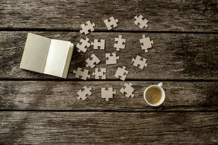 problem solution: Top view of puzzle pieces scattered on a rustic wooden study desk with cup of coffee and open notepad alongside. Conceptual of education, science and solution to a problem or question. Stock Photo
