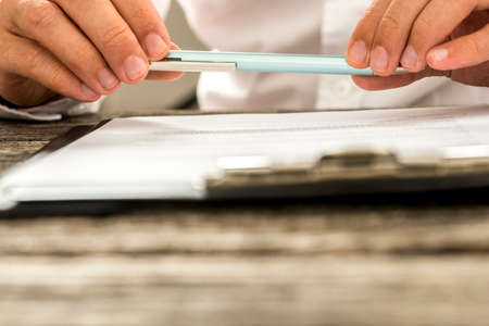 Closeup view of male hands holding pencil over paperwork on clipboard as man reads through terms and conditions. Conceptual of signing business contract, membership or legal document. Banque d'images