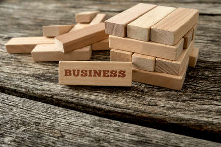 peg board: Word Business written on a wooden peg leaning on a structure build of many blocks. Concept of building and managing business.