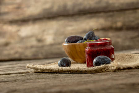 burlap sac: Still life with a jar of home made plum marmalade and wooden bowl full of fresh juicy plums on a burlap cloth lying on a textured rustic wooden desk.