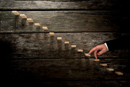 persoonlijke groei: Businessman walking his fingers up wooden steps towards light resembling a staircase in rustic wooden boards in a conceptual image of personal growth, development and achievement.