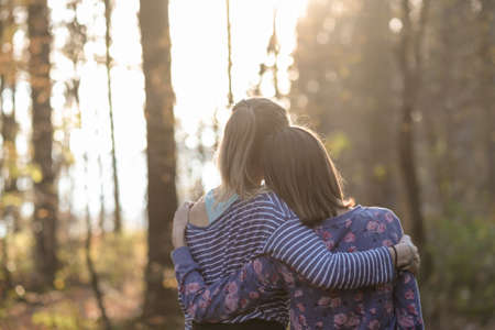 lesbians: View from behind of two girlfriends or a lesbian couple standing in autumn woods leaning on each other with their arms around one another.