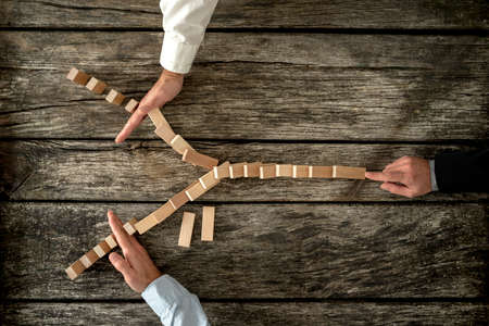Top view of male hand pushing dominos placed in Y shape knocking them down and two other hands stopping them each on one side. Conceptual of crisis management in business. Archivio Fotografico