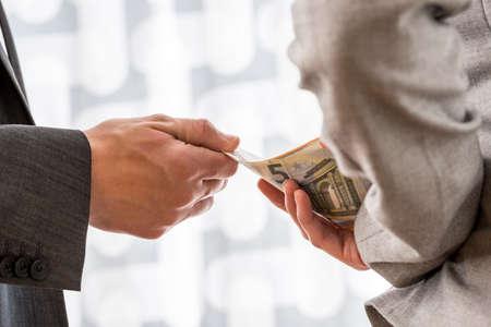 corrupcion: El hombre de negocios o un político de tomar soborno de una compañera de trabajo le entregaba el dinero euro por detrás de su espalda. Conceptual de la corrupción y el soborno.