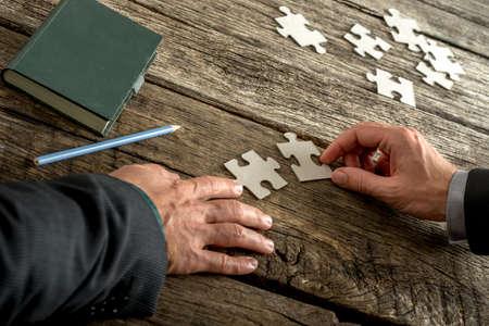 piezas de rompecabezas: El trabajo en equipo y la cooperaci�n entre los dos hombres de negocios, ya que se unen para combinar a juego las piezas del rompecabezas en una textura de escritorio de madera r�stica con la libreta y el l�piz al lado.