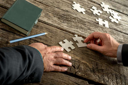 Teamwork and cooperation between two business people as they join forces to combine matching puzzle pieces on a textured rustic wooden desk with notepad and pencil alongside. Stock Photo