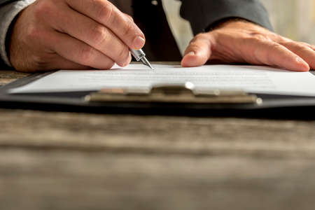 signer: Closeup of businessman signing contract, document or legal papers clipped on clipboard with fountain pen. Stock Photo