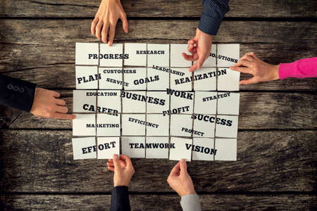 group strategy: Group of six businesspeople creating business strategy by assembling a collage of indispensable elements of successful organization spelled on white cards.