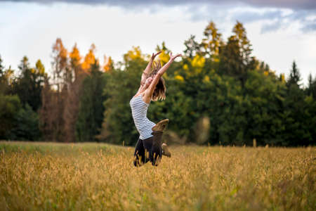 Happy cheerful young woman jumping in the air in the middle of golden meadow with high grass. Conceptual of enjoying life, happiness and life spirit. Stock Photo
