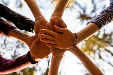 Shot from below of four people stacking hands outside in nature. Concept of unity, togetherness and friendship. Imagens