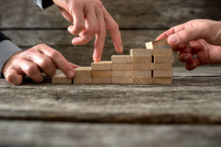 career: Team effort on the way to success - two male hands building stable steps with wooden pegs for the third one to walk his fingers up towards personal and career growth. Stock Photo