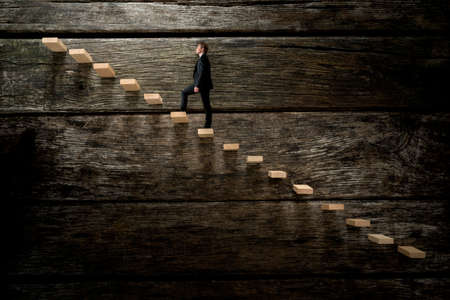 next to: Businessman walking up on wooden stairway, conceptual of development business career. Stock Photo