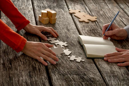 Two partners, man and woman, working on assignment trying to find solution to a problem as one is arranging puzzle pieces and the other making notes.