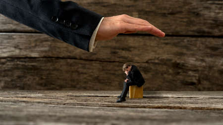 Safety and protection concept - male hand making protective gesture over a desperate man sitting on a wooden cube.