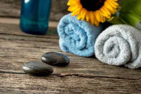 massage stones: Body care and spa still life - two black massage stones with rolled towels, sunflower and moisturizing lotion in background.