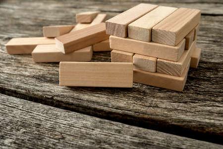 Bloque de madera en blanco apoyado en una estructura hecha de muchos otros bloques con varios de ellos aún yacían esparcidos sobre una mesa de madera rústica con textura. Conceptual de juego libre o puesta en marcha de negocios. Foto de archivo - 48738995