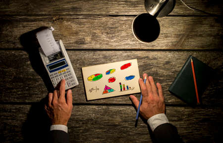 desk lamp: Top view of a man using calculator with printout coming out with a notepad full of colorful charts, graphs and numbers in front of him and pencil in the other hand.