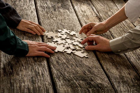 Pile of puzzle pieces lying on textured wooden desk with four hands, male and female, reaching to each take one. Conceptual of teamwork and strategy planning.