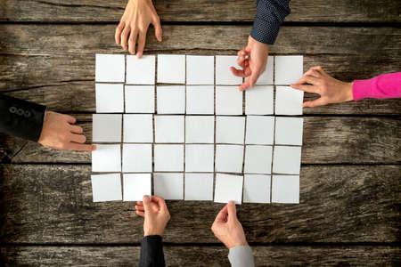 Vista dall'alto di sei mani, maschi e femmine, l'assemblaggio di un collage di carte bianche vuote su texture tavole rustiche in legno. Archivio Fotografico
