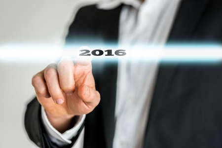 activating: Closeup of male finger activating a 2016 sign on a virtual screen. Conceptual of plan and goals for the coming year and new year resolution. Stock Photo