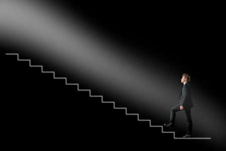黒背景に概念的な階段に光に向かって上向きに歩くビジネスマン。ビジネス開発や希望と信念の概念。