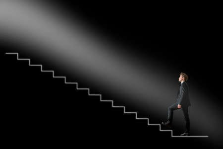 Businessman walking upwards towards the light on conceptual stairway over black background. Conceptual of business development or hope and belief. Stock Photo