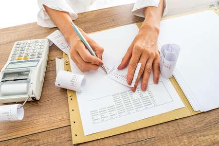 Commercialista o il controllo e il confronto ricevute e dati statistici mentre facendo una relazione finale, che lavora alla sua scrivania con l'aggiunta di macchina a fianco di consulente finanziario. Archivio Fotografico