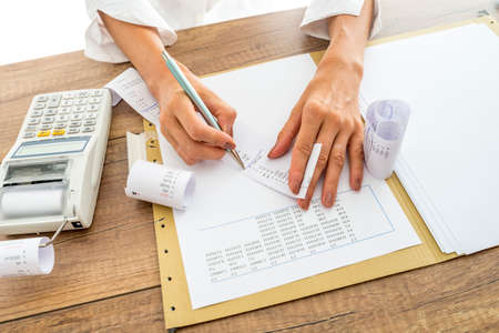 factura: Contador o asesor financiero comprobación y comparación de los ingresos y los datos estadísticos al tiempo que un informe final, que trabaja en su escritorio con una máquina de sumar al lado.
