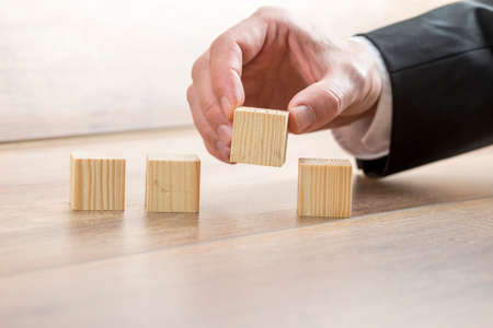 Closeup of male hand in elegant business suit placing four blank wooden cubes in a row.