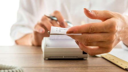 printout: Closeup of a woman holding a printout receipt as it comes out of adding machine while she uses it to make calculations. Stock Photo