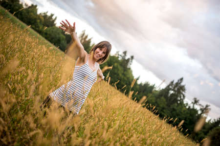 field stripped: Young woman standing in the middle of autumn meadow with high golden grass smiling and holding her arms wide open. Stock Photo