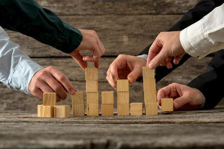 Hände von fünf Geschäftsmann hält Holzklötze sie in eine Struktur platzieren. Konzeptionelle von Teamarbeit, Strategie und Business starten. Lizenzfreie Bilder